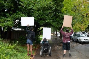 Three people standing with their backs to the camera, at a protest, carrying signs, the middle person is in a wheelchair